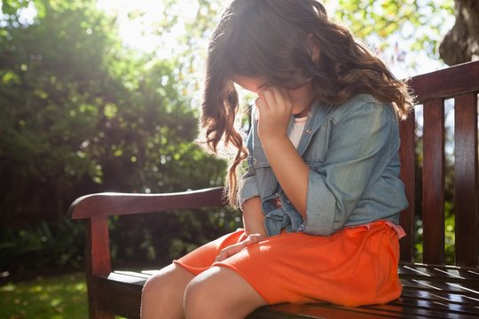 Upset girl crying while sitting on wooden bench