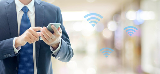 Business man hands using smart phone with wifi icon over blur office background, businessman on phone