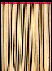 Long wooden matches on a black background