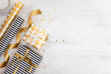 Gift boxes wrapped in black and white striped and golden dotted paper and wrapping materials on a white wood old background. Empty space.