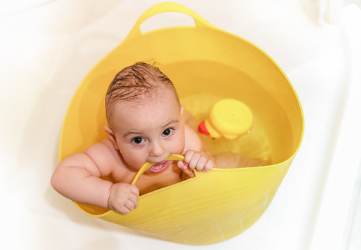 Bathing baby nibbles bucket handle