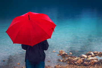 Woman with red umbrella contemplates on rain