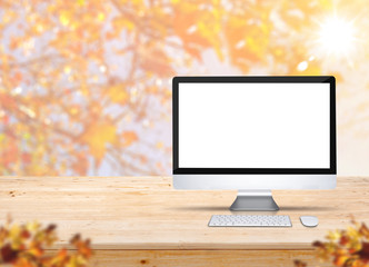 Computer desktop with keyboard and mouse on wood table with blur maple leaf with sunlight and blurred leaves at foreground,Autumn Mock up for display of product,banner for advertise on online