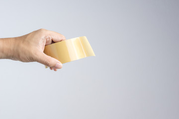 Hand holding brown packaging tape roll