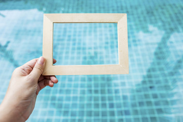 Girl hand holding wooden frame over blurred blue swimming pool water