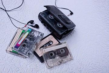 плеер с наушниками и кассеты на серой поверхности