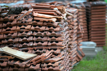 old clay tile roof tiles stacked on wooden pallets. The background for construction restoration and logistics.