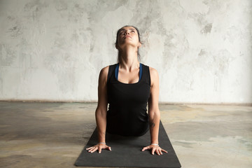 Young attractive sporty woman practicing yoga, stretching in upward facing dog exercise, Urdhva mukha shvanasana pose, working out, wearing sportswear, black top, indoor, wall background