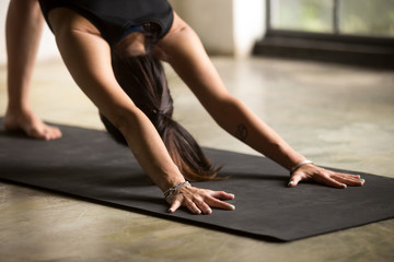 Young attractive woman practicing yoga, stretching in adho mukha svanasana exercise, downward facing dog pose, working out, wearing sportswear, indoor close up, studio floor background
