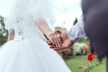 the groom holds his wife's hand