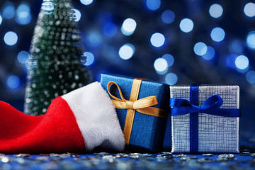 Fir tree, santa hat and christmas gift box or present on blue bokeh background. Magic holiday greeting card.