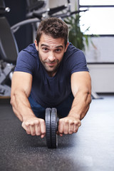 Ab wheel exercise guy looking at camera in gym