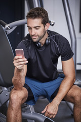 Gym dude texting on Smartphone