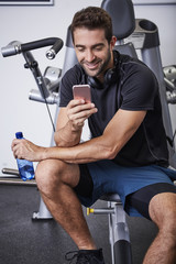 Texting athlete taking a break in gym, smiling