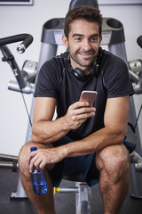 Smiling gym guy using Smartphone and looking away
