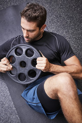 Athlete in gym working out with weight