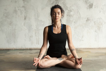 Young woman with tattoo practicing yoga, sitting in Padmasana exercise, Lotus pose, her eyes closed, working out, wearing sportswear, black shorts and top, indoor full length, studio wall background