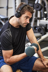 Athlete training in gym with dumbbell, looking away