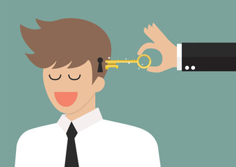 Man holding a key unlocking businessman mind