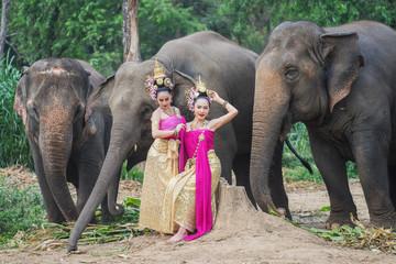 Beautiful Asian Woman wears thai dress with her elephant