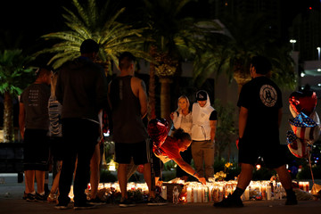 People gather at a vigil on the Las Vegas strip following a mass shooting at the Route 91 Harvest Country Music Festival in Las Vegas
