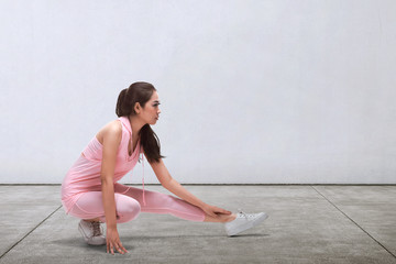 Sporty asian woman doing stretching before running
