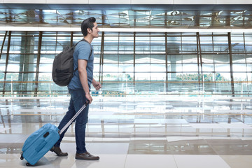 Young asian man walking and pulling the suitcase