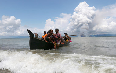 Smoke is seen on Myanmar's side of border as a boat carrying Rohingya refugees arrives to the shore after crossing the Bangladesh-Myanmar border through the Bay of Bengal, in Shah Porir Dwip