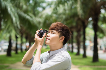 Young asian man photographer taking picture in park