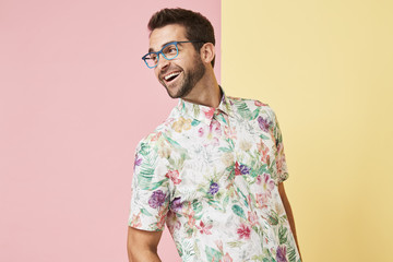 Glasses guy in floral shirt laughing and looking away