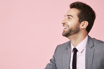 Laughing business guy in profile in pink studio