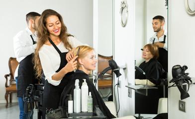 Hairdresser combing hair at barbershop