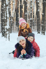 Young mother with two daughters playing in the snow outdoors