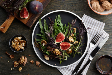Seasonal salad with figs, walnuts and fresh greens on wooden background, top view