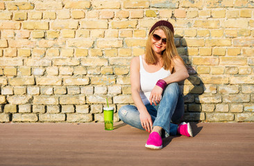 Hipster woman sitting on the ground