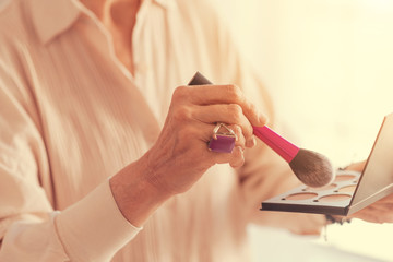 Close up of powder brush in hands of a nice aged woman