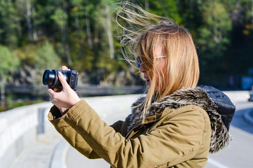 Female, caucasian, blonde model using a camera to take pictures