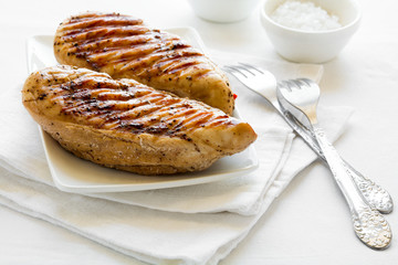 Grilled chicken breast on white table cloth