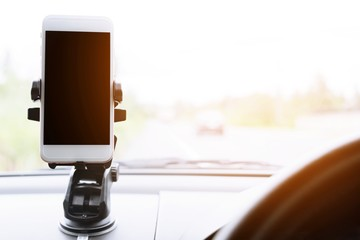 mobile phone with blank screen on console car front windshield holder.