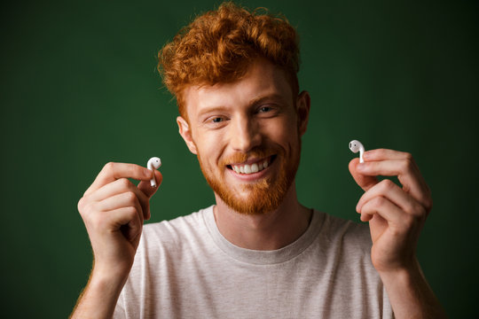 Close-up of young smiling curly redhead bearded young man in white tshirt, showing airpods