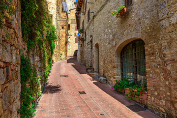 Old cozy street in San Gimignano, Tuscany, Italy. San Gimignano is typical Tuscan medieval town in Italy