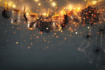 Halloween holiday concept. Masson jars with spiders, baths and wooden decorations Fotoväggar