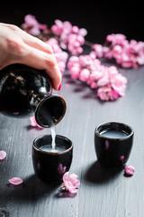 Unfiltered white sake sake in old black ceramics