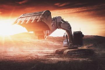 Bagger steht auf Baustelle bei Sonnenuntergang