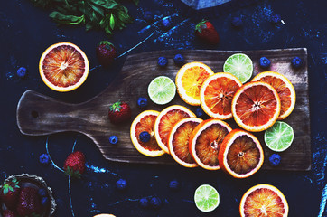 Bloody oranges and limes on dark background, flat lay