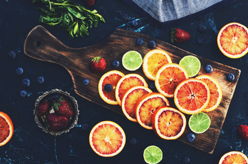 Mix of assorted citrus fruits - red oranges and limes on wooden cutting board, flat lay