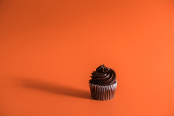 Chocolate cupcake on orange background.