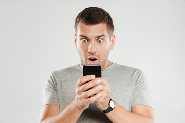 Shocked man chatting by mobile phone.