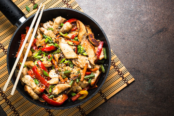 Chicken stir fry with vegetables at stone background. Top view copy space.