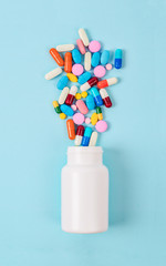 Pills pouring out of the white bottle.